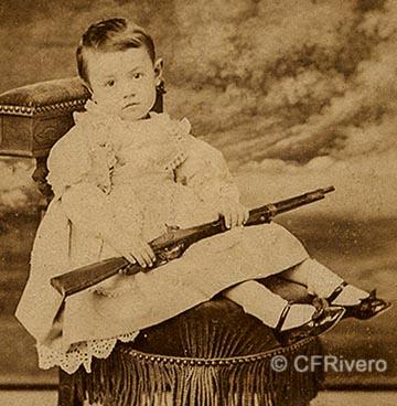Nal y Cia. Niña sentada con escopeta de juguete. Cádiz, h. 1865. Carte de visite en albúmina. (CFRivero)